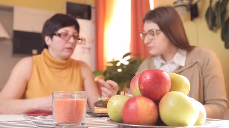 зрелом возрасте : mom and young daughter with glasses drink tea or coffee in the kitchen and eat cakes, talk, laugh. In the foreground plate with apples Стоковые видеозаписи