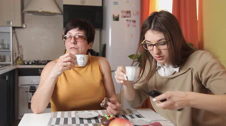 eufória : mom and daughter with glasses watching the news on TV and drink tea or coffee. Something happens and the daughter calls Stock mozgókép