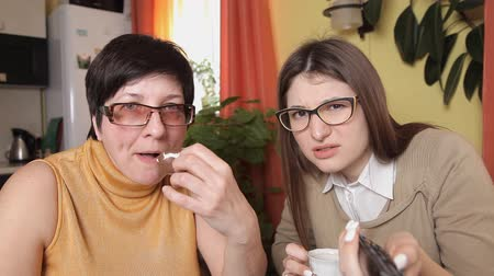 euforia : mom and daughter with glasses watching TV, drinking tea, coffee, eating cakes switch channels remote control and react violently. looking into the camera Vídeos