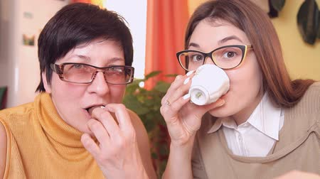 eufória : mom and daughter with glasses watching TV, drinking tea, coffee, eating cakes switch channels remote control and react violently. looking into the camera Stock mozgókép