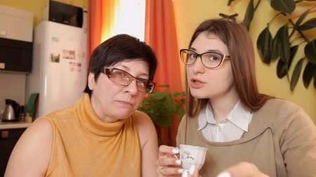 alku : mom and daughter with glasses watching TV drinking tea and eating cakes. happy scored a goal. react violently. looking into the camera Stock mozgókép