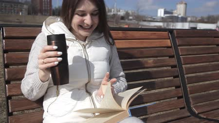 concerned girl : a beautiful girl in a tracksuit in the Park on the bench reading a book and drinking coffee from a thermal mug. laughs from Comedy