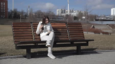 interessado : a beautiful girl in a tracksuit in the Park on the bench reading a book and drinking coffee from a thermal mug