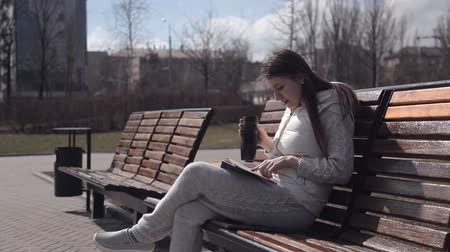 обеспокоенный : a young girl in a tracksuit in the Park on the bench reading a book and drinking coffee from a thermal mug. Turn the pages