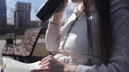 concerned girl : a young girl in the Park on a bench reading a book and drinking coffee from a mug. close up