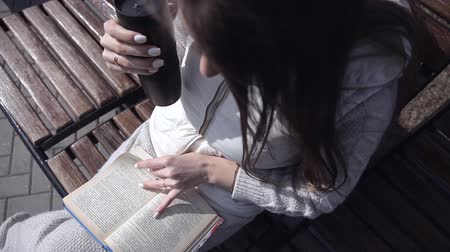 betrokken : a young girl in the Park on a bench reading a book and drinking coffee from a mug. the view from the top Stockvideo
