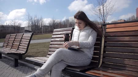 tea bag : a young girl in a tracksuit in the Park on the bench reading a book and drinking coffee from a thermal mug. Turn the pages