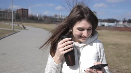 elvihető : A beautiful girl walks in the Park drinking coffee from a thermal mug and texting on the phone, smiling Stock mozgókép