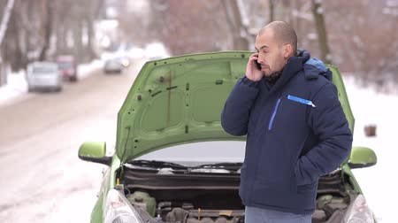 meteliksiz : Snowy winter. A man calls a tow truck on the background of a broken car with an open hood Stok Video