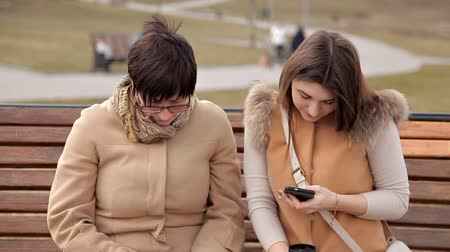 assentado : Mother and daughter sitting in the park to communicate, use mobile phone. Nature, relationships Stock Footage