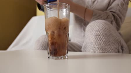 pint glass : A girl sits on a couch and pours a cola into a glass Stock Footage