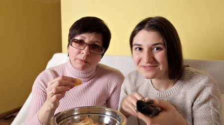 kola : Mom and her daughter eat chips while drinking TV and drink cola. Cozy atmosphere at home