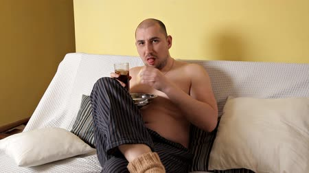 グリース : A fat, bald, lazy man eats potato chips and drinks cola, sitting on the couch without outerwear. Sleazy man. Harmful food