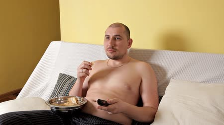 kalori : Lazy, bald, chubby fat man without outerwear is watching TV and drinking Coca Cola with chips lying on the sofa. Fat man leads the wrong lifestyle