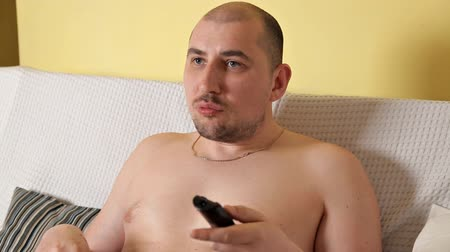 snoepen : Lazy, bald, chubby fat man without outerwear is watching TV and drinking Cola with chips lying on the sofa. Fat man leads the wrong lifestyle