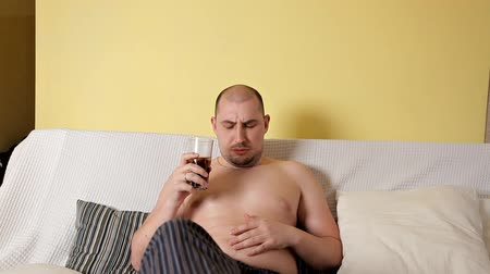 塩漬けの : Lazy, bald, chubby fat man without outerwear is watching TV and drinking Cola with chips lying on the sofa. Fat man leads the wrong lifestyle