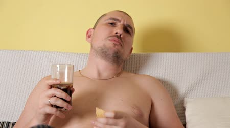 snoepen : Bald nasty fat man is lying on the sofa, watching TV and eating chips and Cola