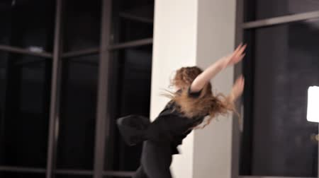 gymnastics : A young girl in a black dress rehearsing dance, the lady is engaged in modern style. Energy, hall, window, dance Stock Footage