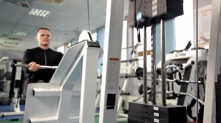 elevação : The muscles of the back. Men train on the rowing machine in the gym. A man raises a heavy weight in the gym. The training