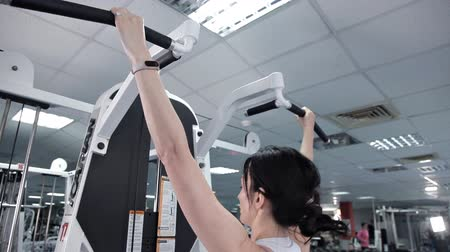 pulling up : Sporty woman doing exercises the muscles of the back of the hands weights at the gym. The turnstile, the girl exercising on the treadmill in the fitness center