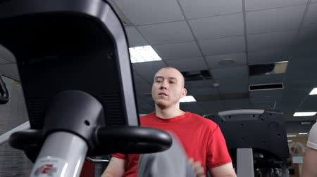 stationary : Fitness men working out with stationary bike in gym