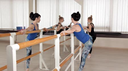 acrobata : Beautiful young women performing splits stretching in the rehearsal room. Slender girls stand in front of the mirror and trains Stock Footage