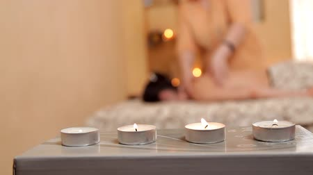 ayurveda : A warm and magical atmosphere of the luxury Spa woman receiving massage of shoulder and back. Burning candle