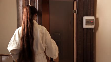 bodywarmer : A young girl in a white robe opened the glass door and entered the sauna
