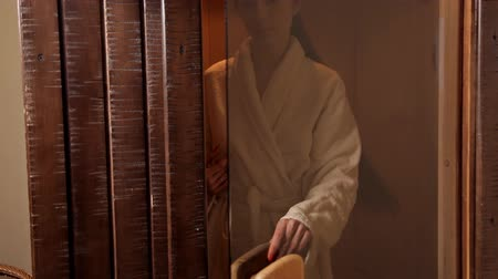abriu : A young girl in a white robe opened the glass door and entered the sauna