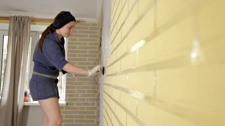 kielnia : A girl with a putty knife, spackling paste.A method of applying a layer of a spatula and working with putty paste. Repair of the wall in the apartment, flat wall