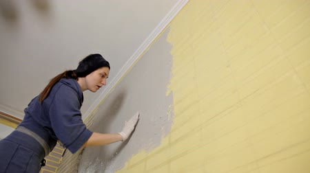 шпатель : A girl with a putty knife, spackling paste.A method of applying a layer of a spatula and working with putty paste. Repair of the wall in the apartment, flat wall