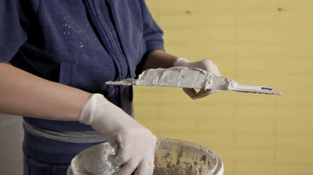 plasterer : Young girl gaining putty paste from a bucket on a spatula. Home repair