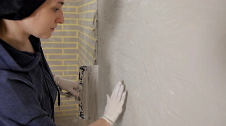 barvivo : Young girl putty, paste on the wall, and then aligns the putty on the wall with his hand. Repair, smooth walls Dostupné videozáznamy