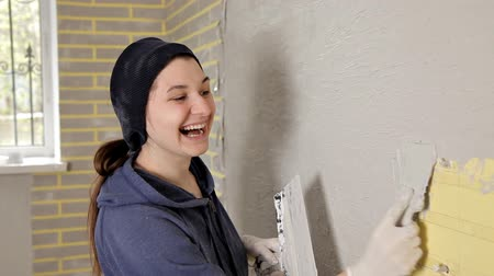 riparazioni : happy smiling girl holding spatula and doing repairs in her apartment