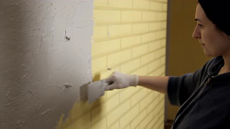 decorador : Girl in white gloves puts a wall in front of the repair. Spatula, plaster. Smooth walls