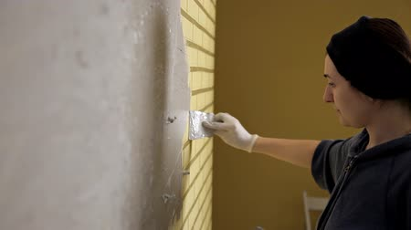 plasterer : Girl in white gloves puts a wall in front of the repair. Spatula, plaster. Smooth walls