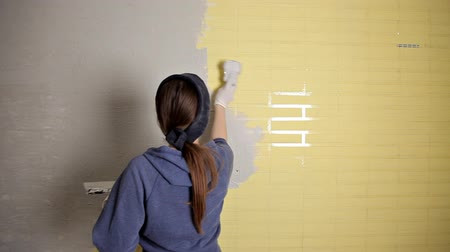 leveling : Home repair. The girl spreads the plaster on the wall with a large metal spatula to align the plaster filler on the wall. Repair work Stock Footage