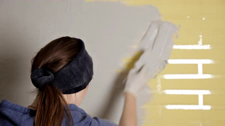 kielnia : Home repair. The girl spreads the plaster on the wall with a large metal spatula to align the plaster filler on the wall. Repair work Wideo