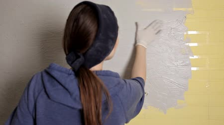 スプレッド : Home repair. The girl spreads the plaster on the wall with a large metal spatula to align the plaster filler on the wall. Repair work 動画素材