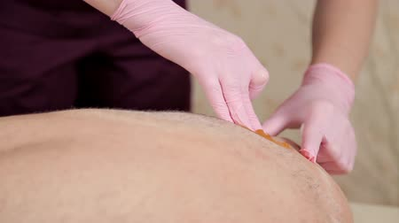 depilacja : The process of waxing the male back. Procedure sugaring