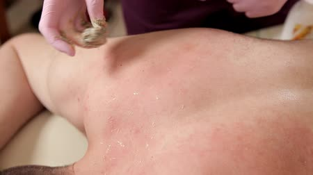 epilating : The young man removes the hair on the back of his head in a beauty salon. Epilation