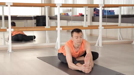 продвинутый : A person practicing advanced yoga. A strong man performing yoga exercises in the Studio