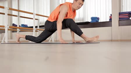 flexibilidade : Athlete-man makes torso turns, sitting on the floor in the gym, yoga exercises.Health, life, flexibility