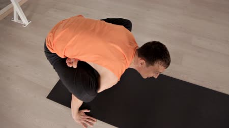 meditující : A man sitting on a yoga Mat and doing exercises in a special room. The concept of health and strength