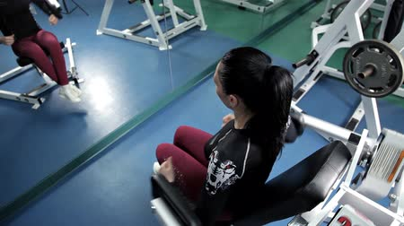 contra : Fitness - powerful casual woman lifting weights in gym club.A beautiful girl will perform pull-ups in the gym. Fitness. Body-building Stock Footage