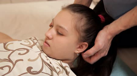 ayarlama : Close-up of a little girl at an osteopathic therapy session. The therapist manipulates the childs head. Massage at the Spa Stok Video