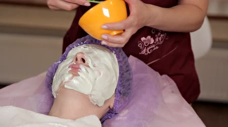 опытный : An experienced cosmetologist prepares a healthy mask for the client. She gets up and touches the face with a brush. A young woman lies with her eyes closed. Facial skin care.Alginate mask Стоковые видеозаписи