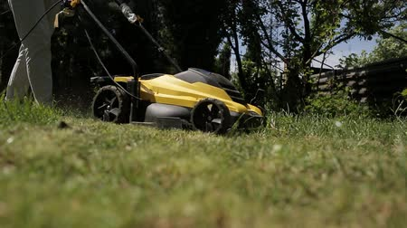 trimmelés : the girl is mowing an uneven lawn with yellow lawnmower barefoot