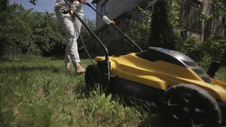 desigual : the girl is mowing an uneven lawn with yellow lawnmower barefoot