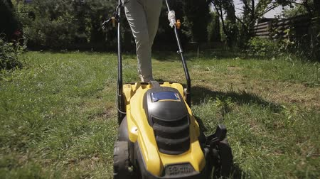 mow : the girl is mowing an uneven lawn with yellow lawnmower barefoot
